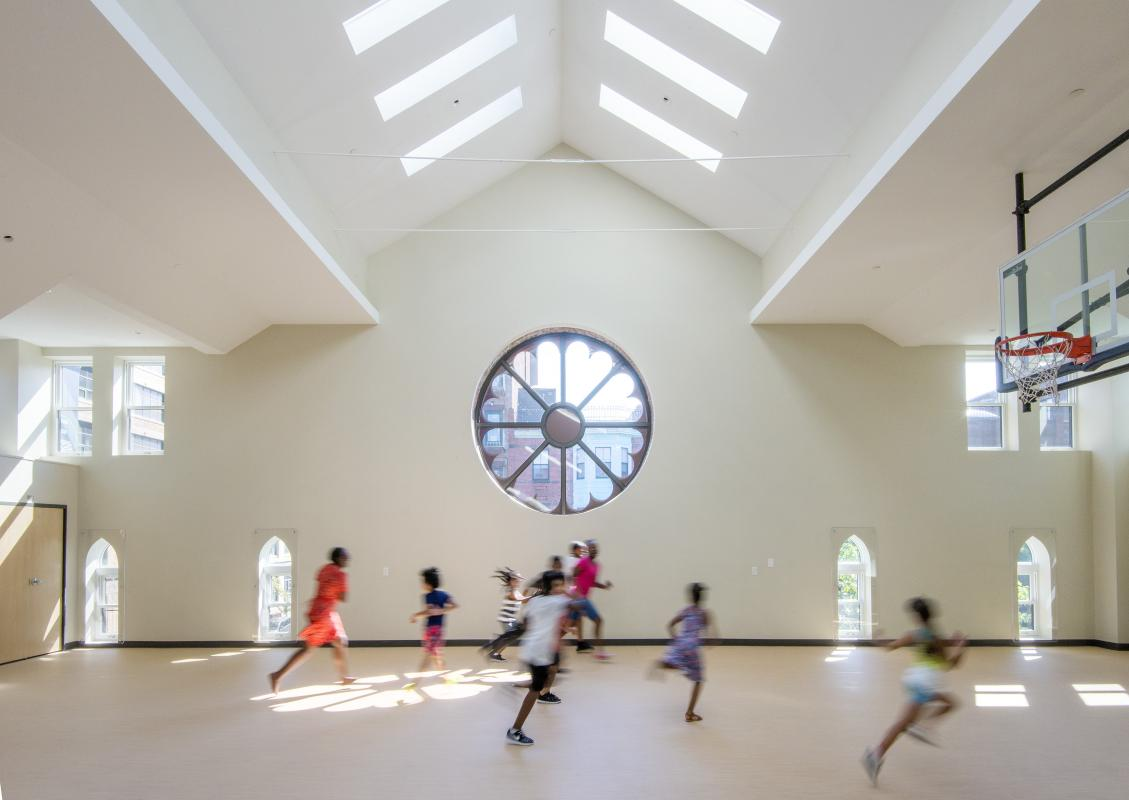 Gym interior showing vaulted church ceiling with skylights, and rose window