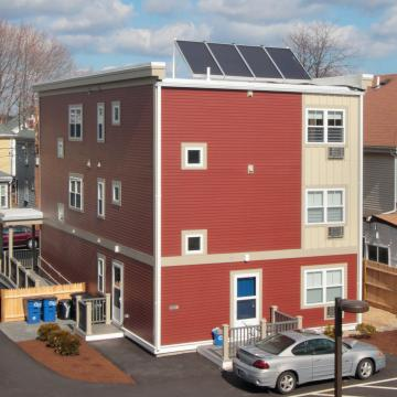 Elevated view of rear corner exterior with roof solar panels