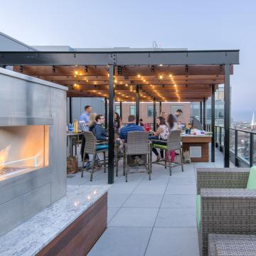 Pergola beyond outdoor fireplace, with tables and chairs