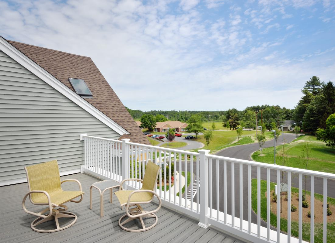 Roof deck with table and chairs, view of fields and woods