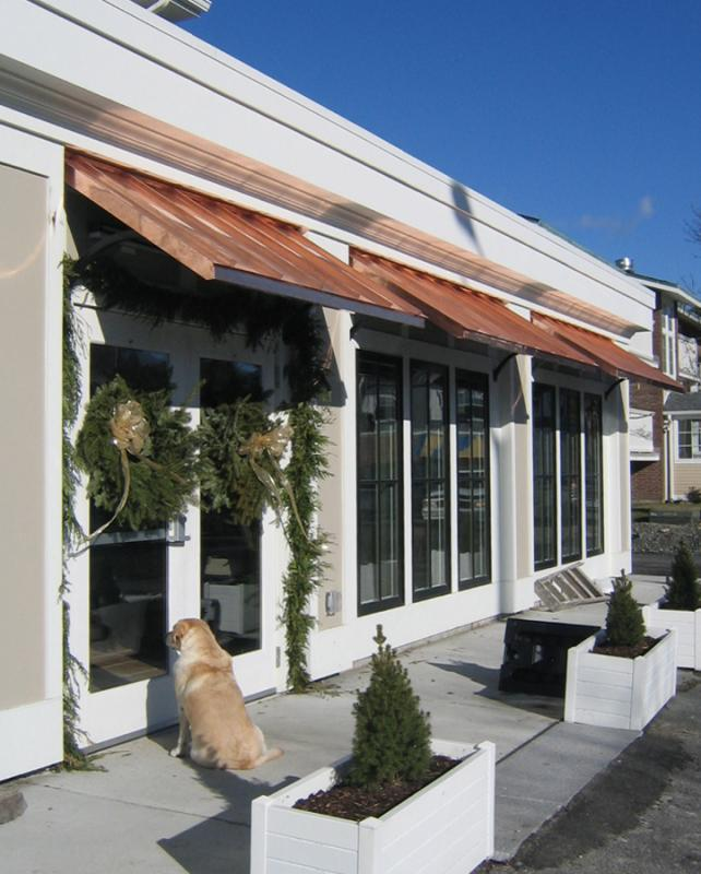 Storefront with copper awnings and golden retriever looking into window