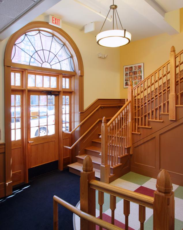 Lobby interior with arched doorway and wooden staircase