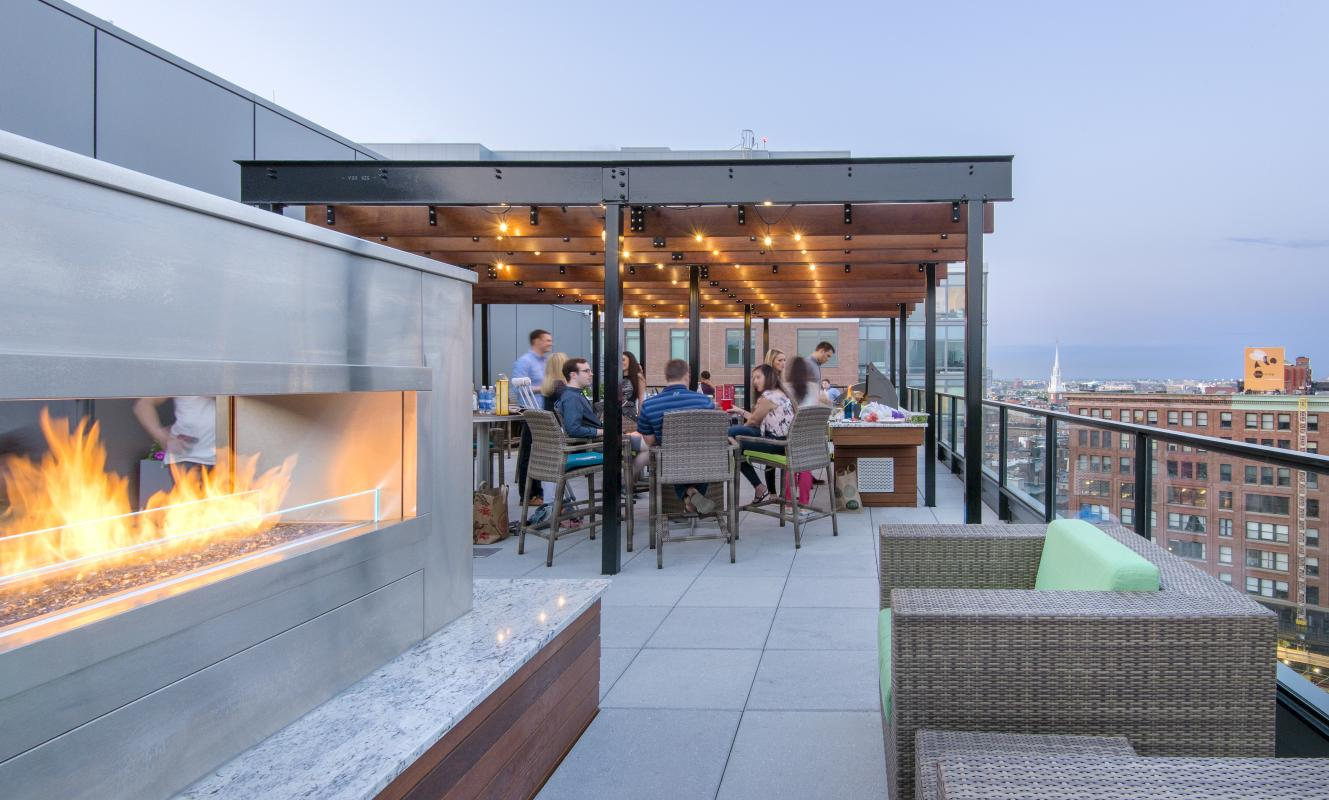 Outdoor fireplace with chairs; pergola beyond with tables and chairs