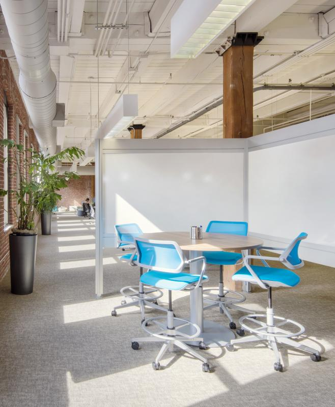 Partitioned meeting area with open office beyond, with row of windows in brick wall